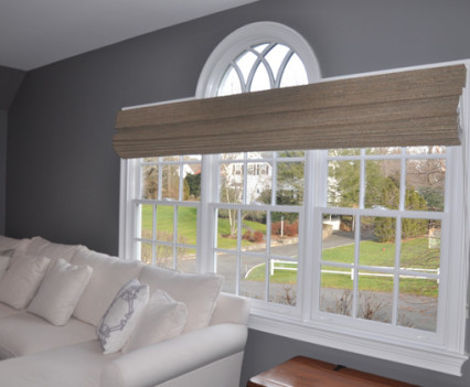 long woven wood blinds on triple windows in living room